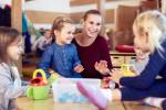 Eine Erzieherin spielt lachend mit vier kleinen Kindern an einem Tisch