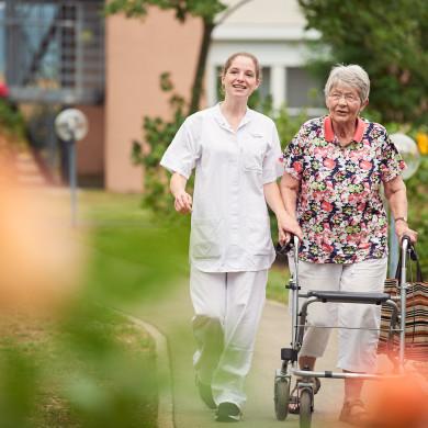 Eine Seniorin läuft mit einer Betreuerin im Kurpark