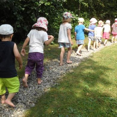 Kinder laufen vorsichtig durch den Barfußpark