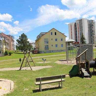 Im Vordergrund ein Spielplatz und im Hintergrund ein Wohngebiet in Bästenhardt
