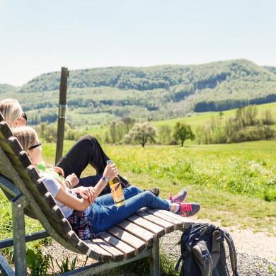 Wanderer ruhen sich auf einer Bank mit herrlichem Blick auf die Landschaft aus