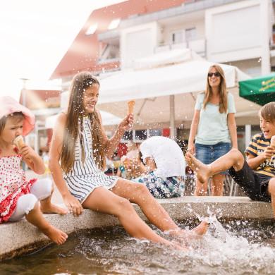 EIne Familie kühlt sich beim Eisessen am Brunnen in der Stadtmitte ab