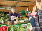 Eine freundliche Verkäuferin beim Gemüseeinkauf auf dem Wochenmarkt