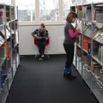 Im Sachbuchbereich können Kinder viel Neues entdecken. Das Kind im Vordergrund such sich noch ein Buch aus, hinten auf dem Stuhl hat sich ein Mädchen bereits für ein Sachbuch entschieden