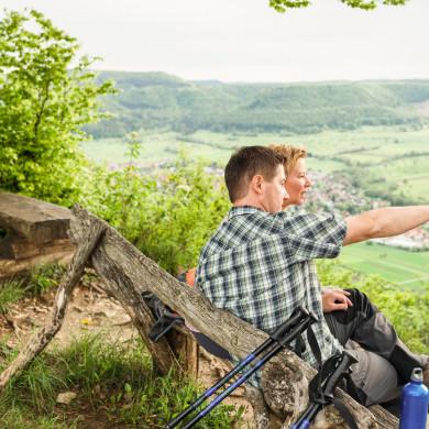 Wanderer ruhen sich auf einer Bank an einer Aussichtsplattform im Wald aus und schauen auf die Stadt