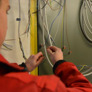 Ein Elektroniker bei der Arbeit mit Kabeln