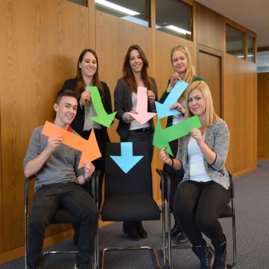 Fünf Auszubildende zeigen mit bunten Pfeilen auf einen leeren Stuhl