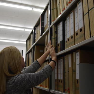Auszubildende vor einem Aktenschrank im Archiv