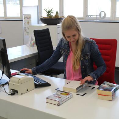Eine Auszubildende bei der Arbeit an der Ausgabetheke in der Bücherei