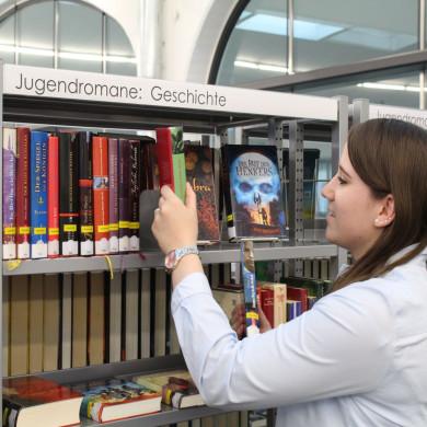 Eine Auszubildende vor einem Bücherregal in der Bücherei