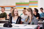 Schülerinnen und Schüler sitzen in der Schule die beiden Mädchen im Vordergrund lachen gemeinsam