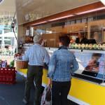 Einkaufserlebnis auf dem Wochenmarkt an einem Metzgerei-Wagen mit zwei Kunden und einer freundlichen Verkäuferin