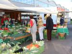 Auf dem Wochenmarkt werden frische Produkte verkauft. Man sieht einen Stand mit Obst und Gemüse sowie Verkäuferinnen und drei Besucher. Im Hintergrund sieht man einen weiteren Verkaufsstand