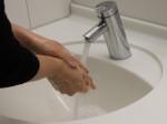 Man sieht ein Waschbecken in dem Hände gewaschen werden