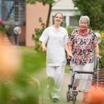 Pflegekraft mit Seniorin beim Spaziergang