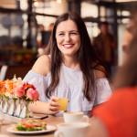 Eine lachende junge Frau sitzt mit einer anderen Frau im Lokal und trinkt einen Saft