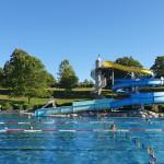 Schwimmer genießen das Wasser im Freibad im Hintergrund sieht man eine große Rutsche, eine Liegewiese mit Bäumen und blauer Himmel