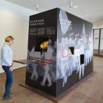 """Museumsleiterin Dr. Franziska Blum schaut sich den Erinnerungskubus zum """"Mössinger Generalstreik"""" im Foyer des Rathauses an"""