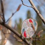 Ein buntes Glasosterei hängt an einem Strauch