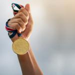 Eine Hand hält eine goldene Medaille in die Luft. ©Naypong Studio - stock.adobe.com