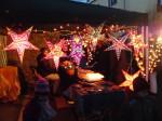 Schöne, leuchtende Sterne hängen vor einem Stand auf dem Weihnachtsmarkt