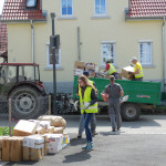 Vereinsmitglieder tragen Arbeitskleidung und gelbe Warnwesten. Sie sammeln Altpapier von einem Hof auf einem Traktoranhänger, der vor einem gelben Haus an der Straße steht.