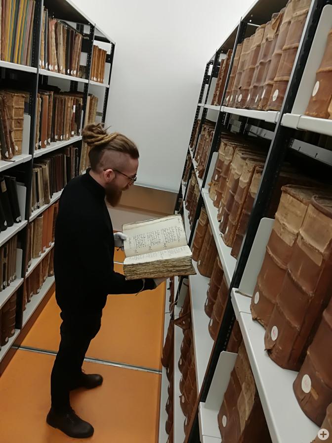 Stadtarchivar David Bauer nimmt Einsicht in einen der dicken, ledergebundenen Bände der Inventuren und Teilungen