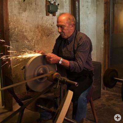 Hans Streib schleift ein Messer am alten Schleifmechanismus