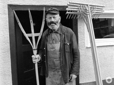 Wilhelm Wagner mit Gabel und Rechen vor seinem Haus