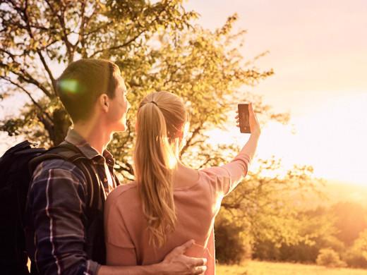 Ein junges Paar macht ein Selfi im Hintergrund sieht man den Sonnenuntergang und Bäume